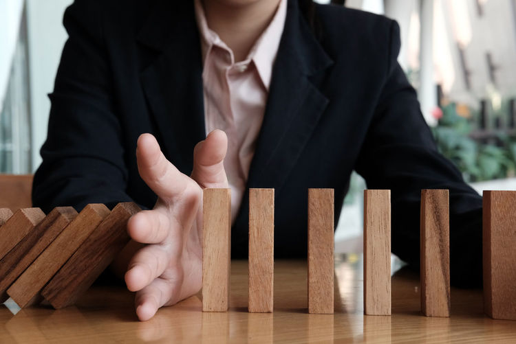 hand stopping effect of domino continuous toppled. businessman protecting falling wood block. solution & strategy in business. problem solving concept Problem Blocks Breaking Continuity Domino Dominos Falling RISK Action Balance Blocking  Business Business Person Businessman Change Conflict Continuous Effect Failure  Hand Intervene Management Protection Table Wood - Material