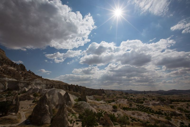 Scenic view of cappadocia against cloudy sky on sunny day
