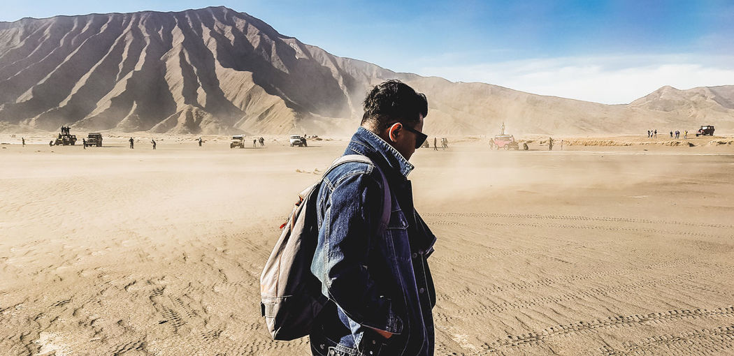 Man standing on desert against mountain