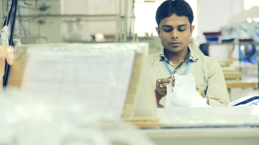Young man stitching cloth by table