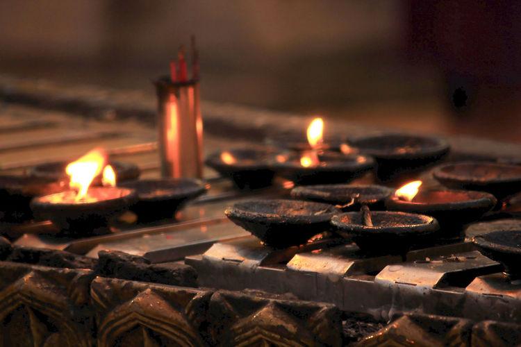 Lit tea light candles in temple against building
