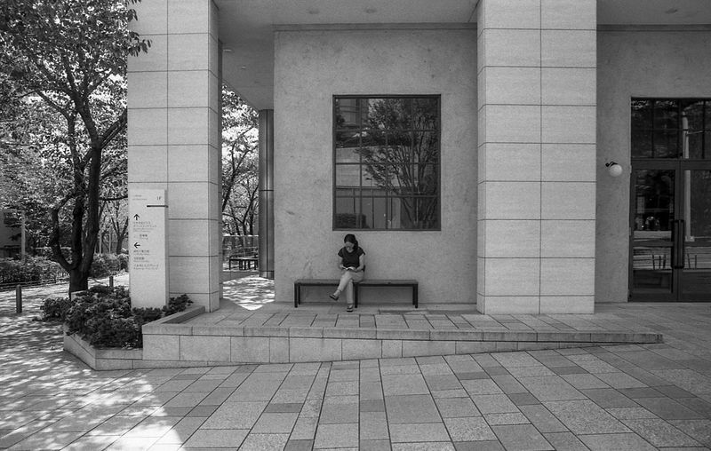 Street Photography Streetphotography Tokyo Black And White Blackandwhite Film Photography Film Architecture Built Structure Building Exterior One Person Real People Day Building Full Length Adult Lifestyles Women Window Entrance Standing Footpath Plant Outdoors Tree Architectural Column
