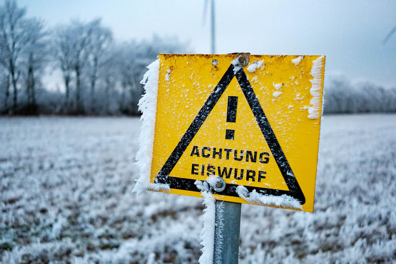 Close-up of yellow sign on snow covered field