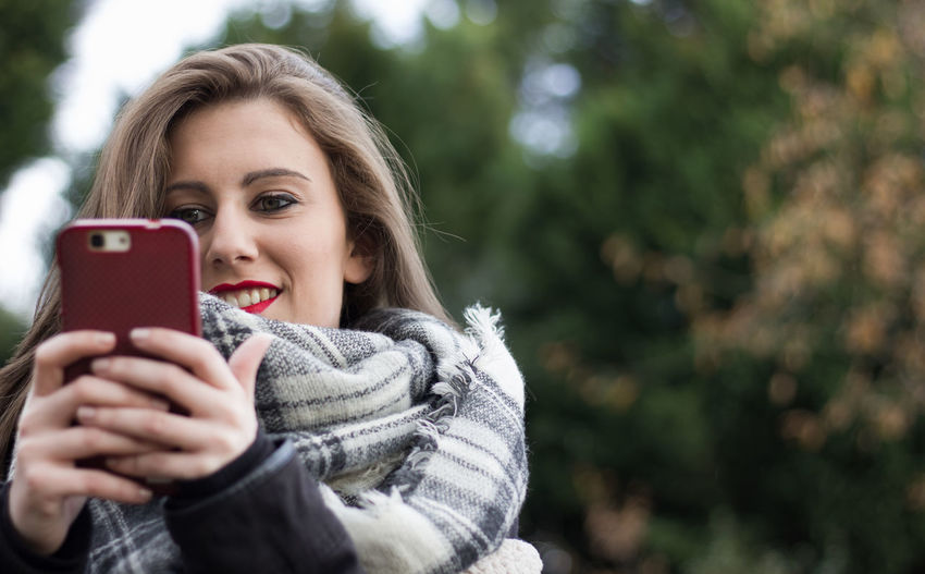 Portrait of smiling young woman using smart phone during winter