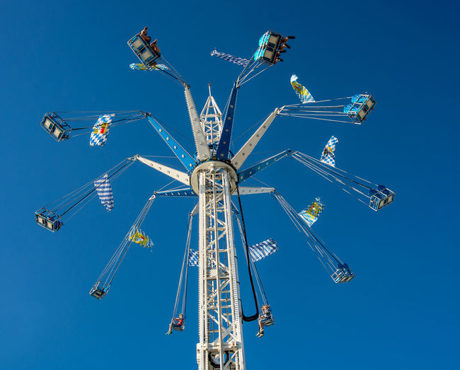Low angle view of chain swing ride against blue sky
