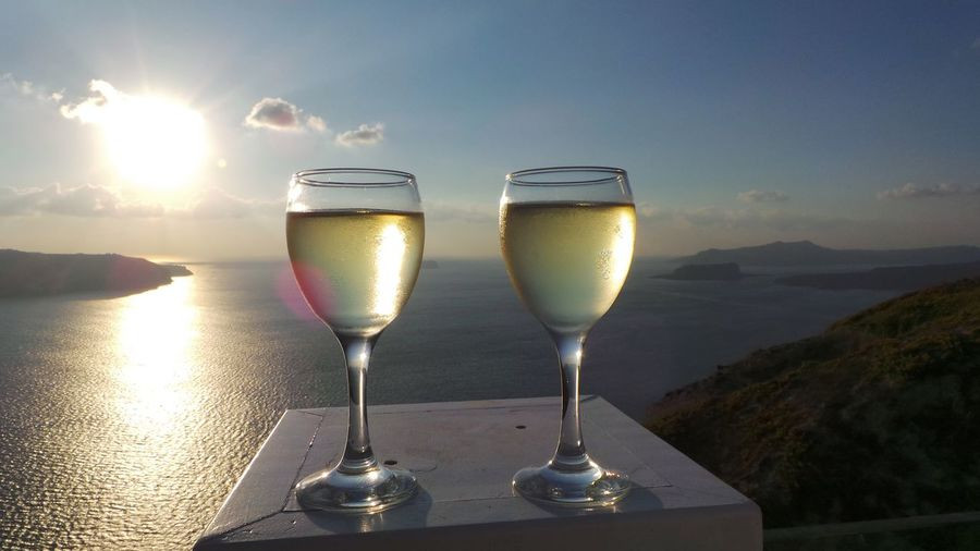 White wine served in glasses on table against sea