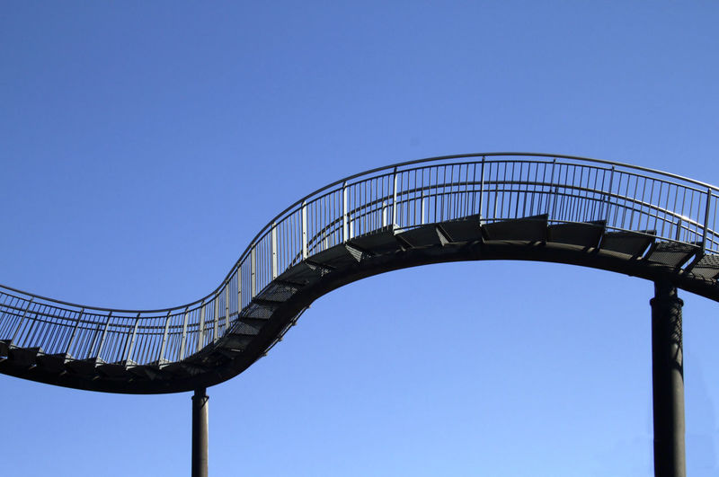 Low angle view of silhouette bridge against clear blue sky