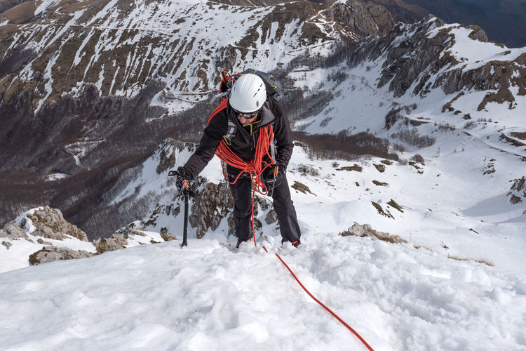 High angle view of man climbing snow covered mountain