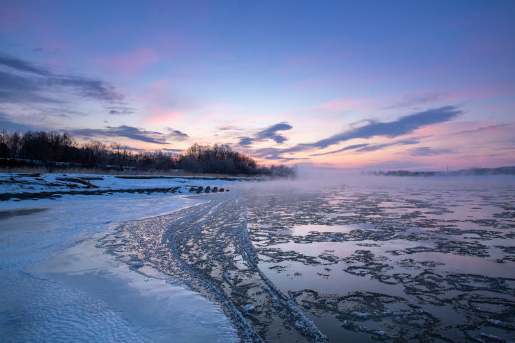 Sky Beauty In Nature Tranquil Scene Water Winter Cold Temperature Tranquility Cloud - Sky Scenics - Nature Snow Nature No People Frozen Non-urban Scene Plant Outdoors Frozen Water River Floating Ice Ice Sunrise Dawn Misty Foggy Foggy Morning