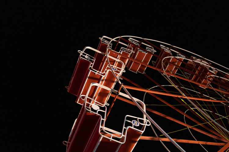 Low angle view of illuminated ferris wheel against black background