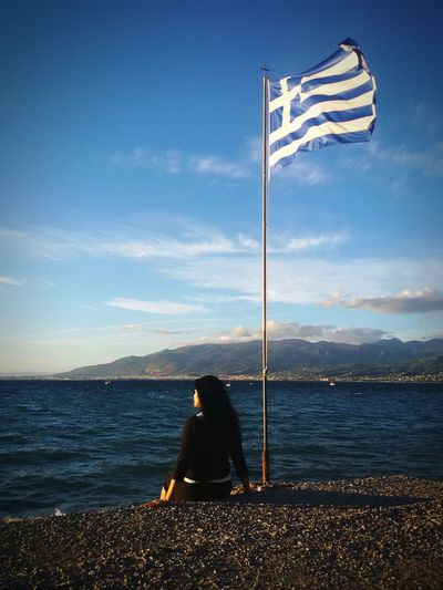 Rear view of woman sitting by greek flag on promenade against sky