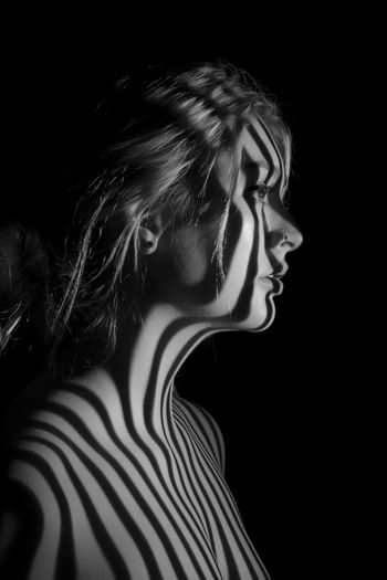 Side view of topless woman looking away over black background