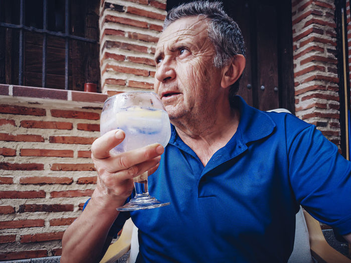 Mid adult man holding drink drinking glass