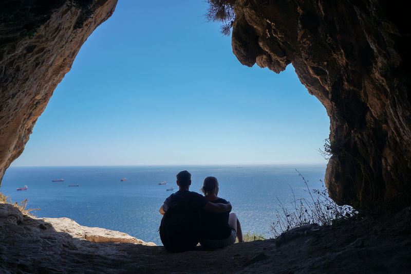 Rear view of couple looking at sea while sitting with arm around against sky