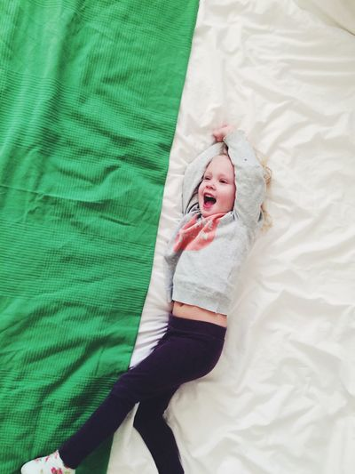 High angle view of cheerful girl lying on bed at home