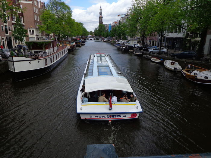 People on passenger craft in canal amidst buildings in city