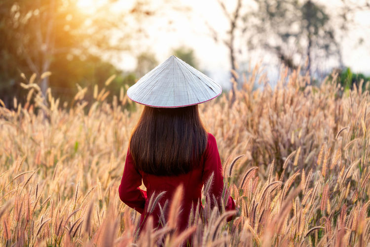 Asian woman wearing Vietnam culture traditional in african fountain flower field. One Person Plant Field Rear View Adult Women Real People Nature Land Hairstyle Sunlight Long Hair Hair Casual Clothing Lifestyles Standing Day Leisure Activity Selective Focus Outdoors Human Hair