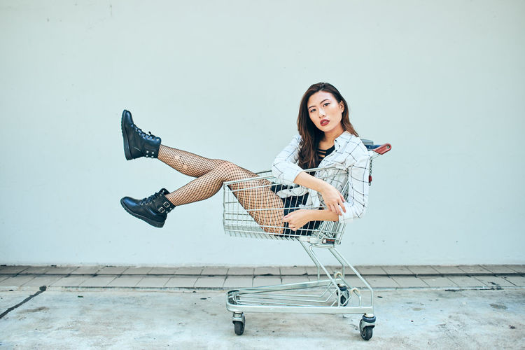Shopping Cart Trolley One Person Casual Clothing Full Length Lifestyles Real People Young Adult Leisure Activity Smiling Young Women Wall - Building Feature Holding Hair Portrait Front View Beautiful Woman Looking At Camera Long Hair Happiness Hairstyle