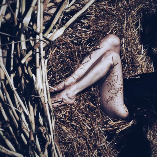 Low section of sensuous woman resting on hay