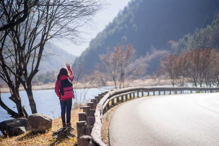 Girl in red winter cloth standing by a road in sunshine, with right hand up. Alone Autumn Hiking Road Signal Sunny Travel Trees Adventure Autumn🍁🍁🍁 Gesture Girl Hand Hitchhiking Lake Long Hair Mountains Outdoor Ride Single Valley Waving Hand