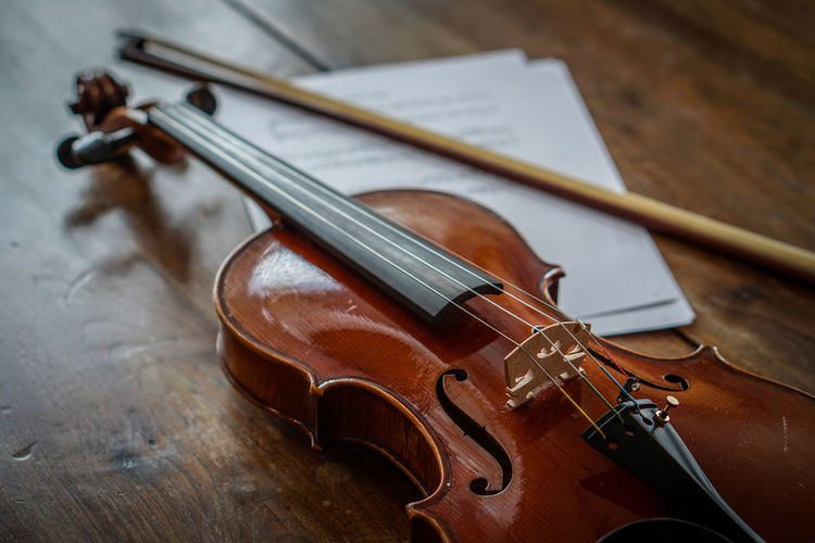 High Angle View Of Violin With Bow On Wooden Table