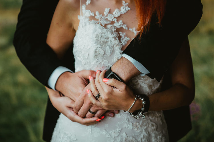 Midsection of bride and bridegroom holding hands