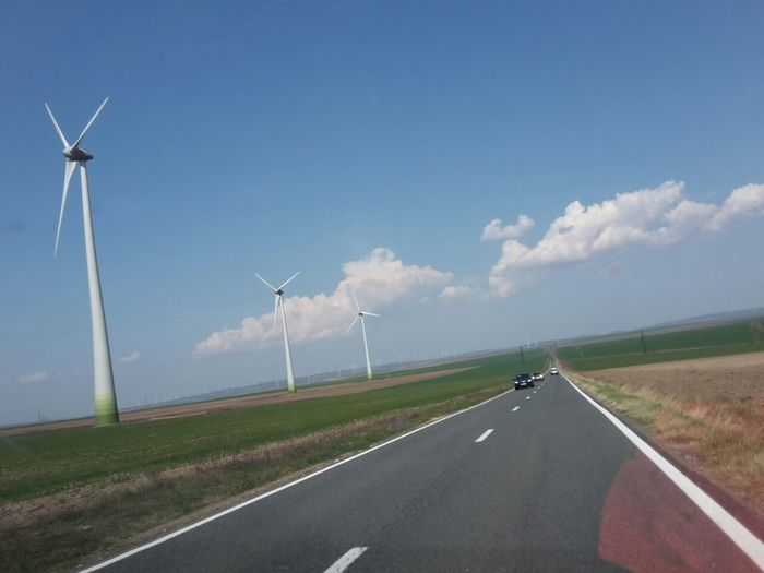 View of windmill on road against sky