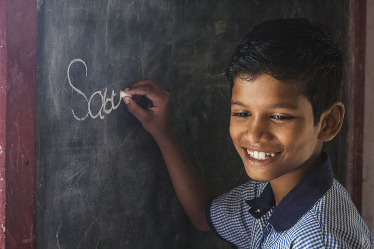 Close-up of boy writing on blackboard