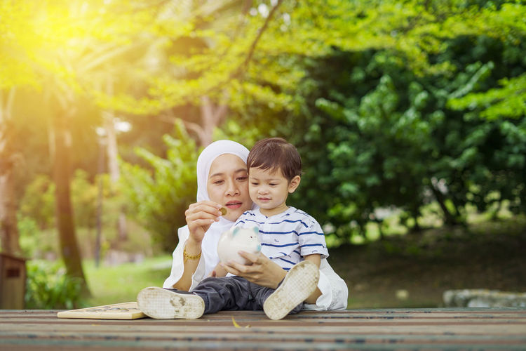 Young woman with her cute son learn how to put coins into piggy bank. Future planning concept. Child Childhood Togetherness Family Males  Men Bonding Son Innocence Two People Boys Offspring Sitting Tree Emotion Full Length Casual Clothing Happiness Portrait Day Positive Emotion Outdoors