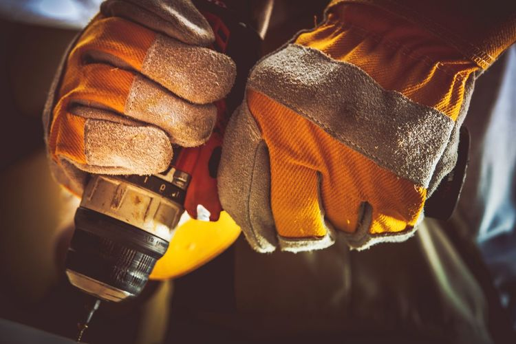 Cropped hands of manual worker using drill