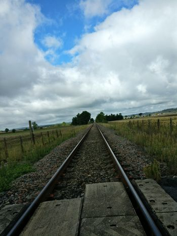 Railroad Track Cloud - Sky Rail Transportation Diminishing Perspective The Way Forward Day Field No People Agriculture Landscape Grass Outdoors Transportation Sky Parallel Rural Scene Nature Scenics Beauty In Nature Lost In The Landscape