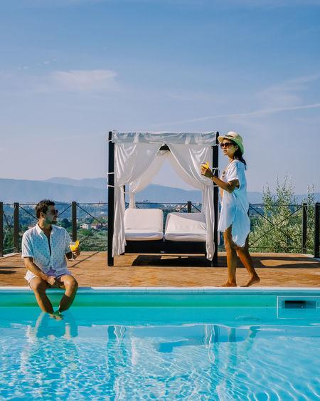 People sitting in swimming pool against blue sky
