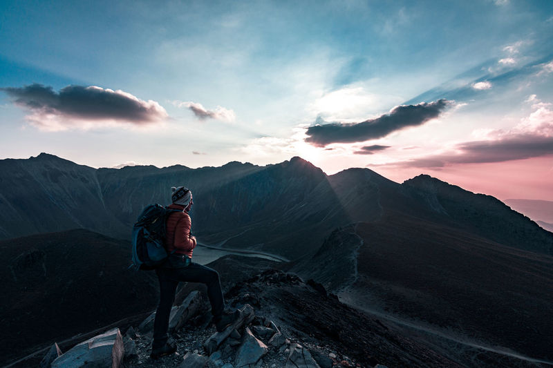 Hiker with backpack standing on cliff against sky during sunset