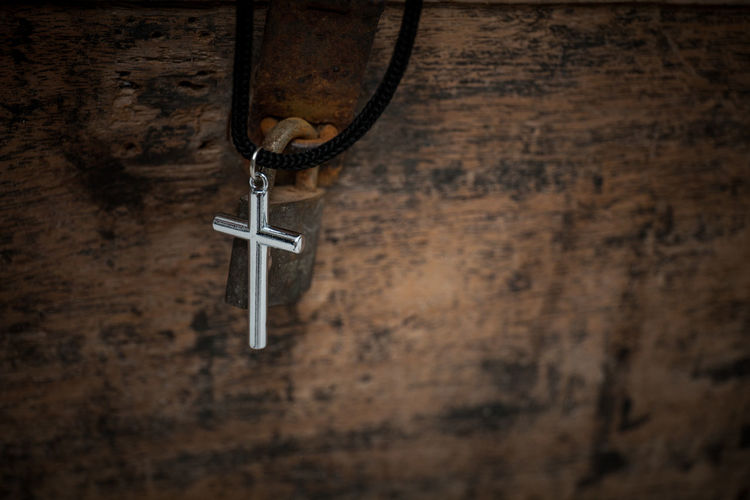 Close-up of cross hanging on wood