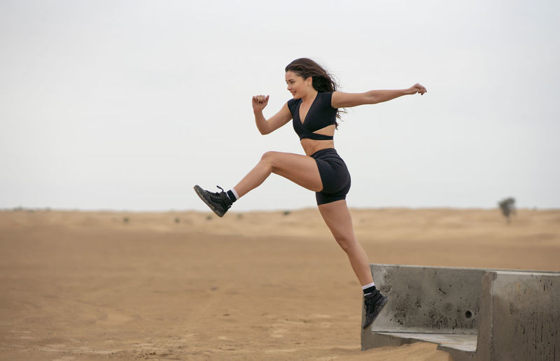 Full length of woman jumping while running on sand