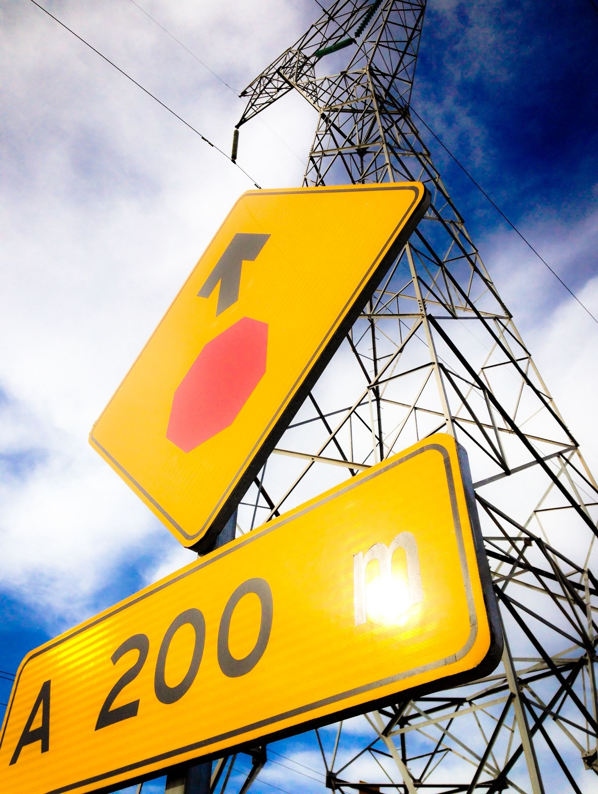 yellow, text, communication, low angle view, western script, information sign, sky, guidance, road sign, sign, information, warning sign, directional sign, capital letter, cloud - sky, arrow symbol, cloud, cloudy, pole, direction