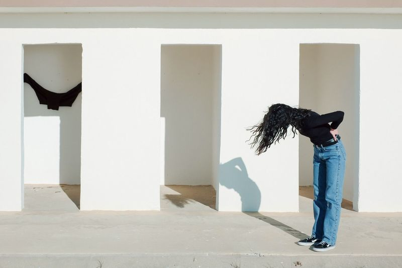 Side view of woman standing against white wall