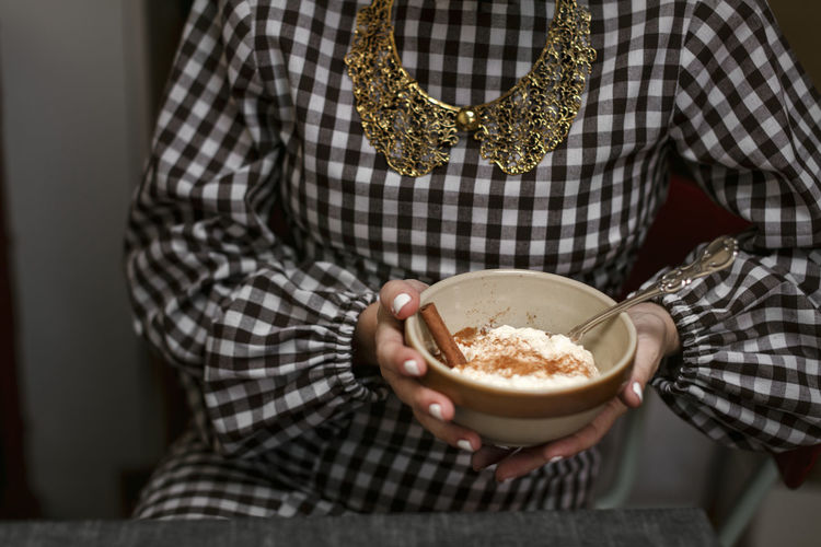 Midsection of woman holding ice cream in bowl