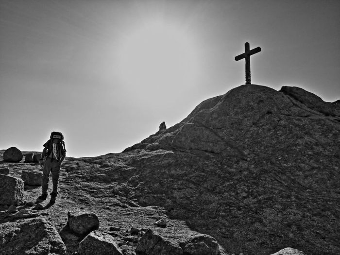 Low angle view of cross on rock against sky