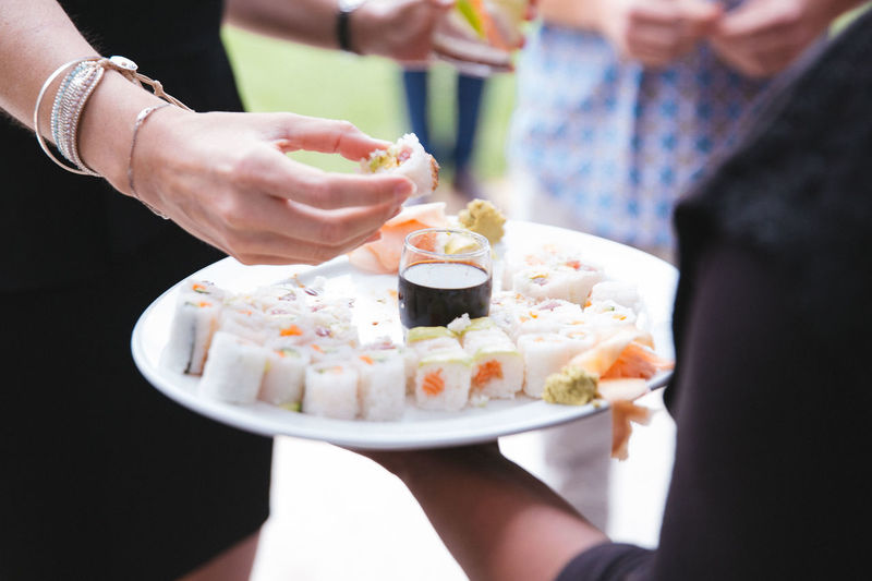 Waiter holding sushis in plate while woman eating