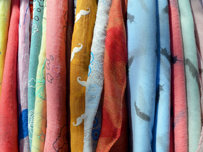 A lot of light scarfs of different colors (red, yellow, orange, blue, green) on a hanger close up Scarf Shawl Neckerchief Clothing Multi Colored Full Frame Choice Variation Backgrounds Close-up No People Textile In A Row Market