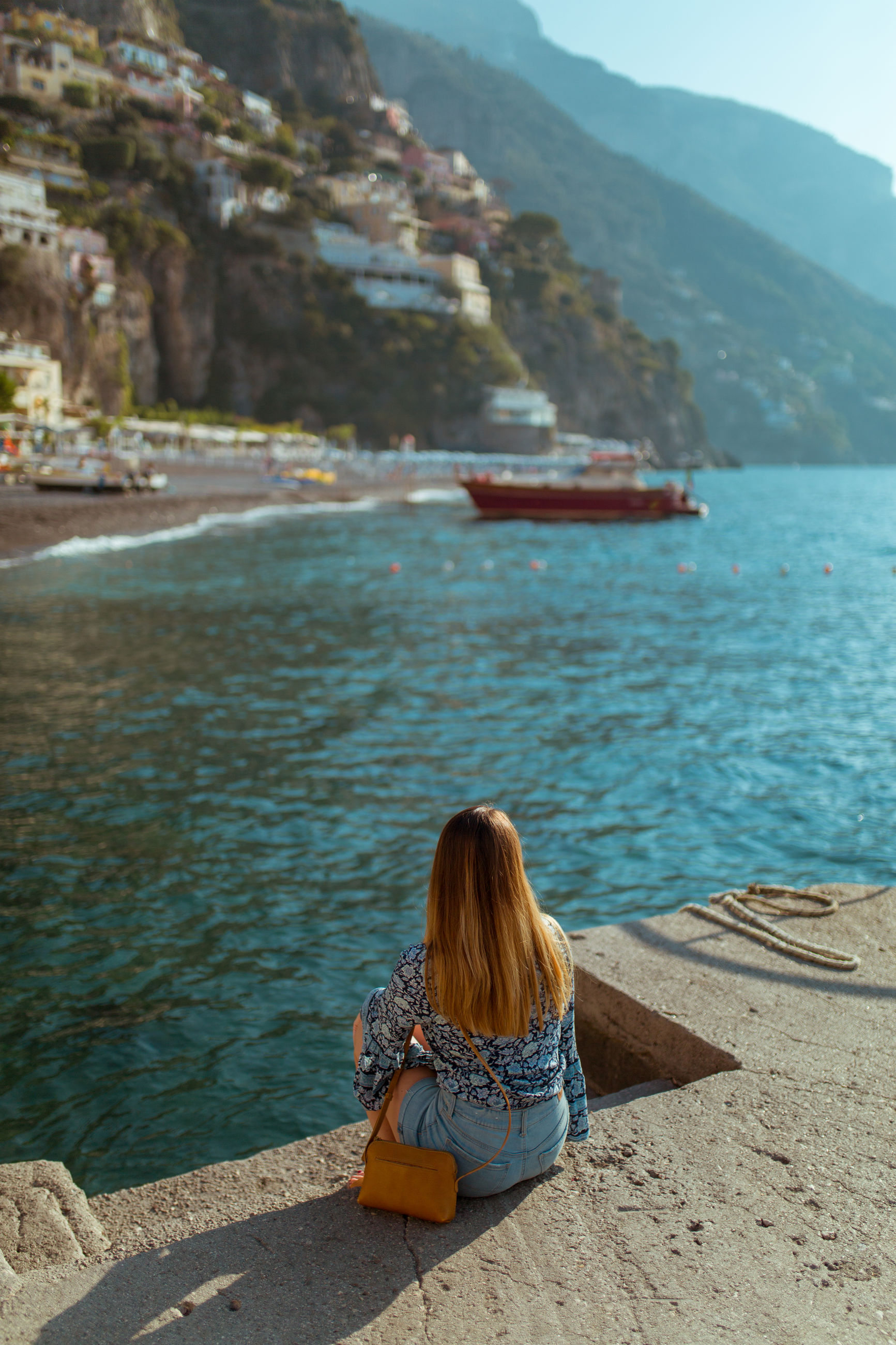 water, one person, sitting, mountain, leisure activity, rear view, real people, lifestyles, women, day, beauty in nature, nature, scenics - nature, adult, sea, relaxation, hair, casual clothing, tranquility, looking at view, outdoors, mountain range, hairstyle