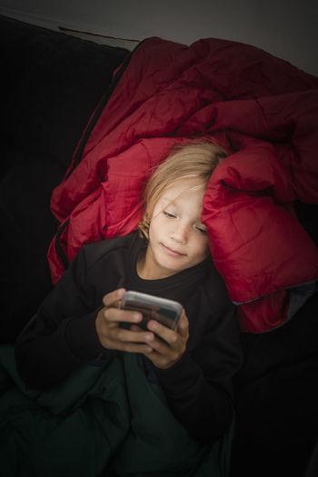 Full length of girl using mobile phone on bed