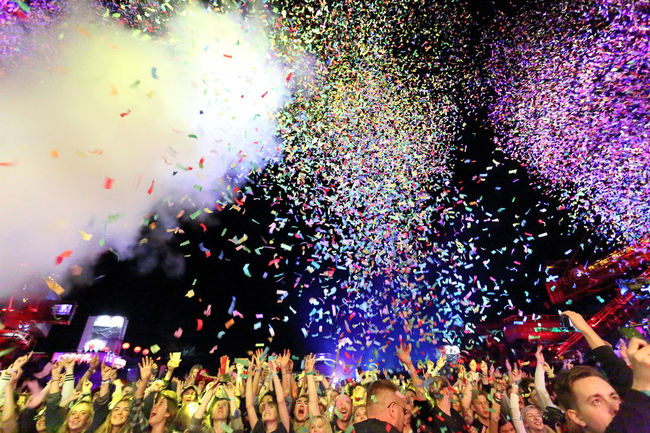 front row concert crowd in confetti shower Arms Raised Celebration Concert Confetti Crowd Event Festival Fog Frontrow Human Hand Large Group Of People Men Multi Colored Night Outdoors Party People Performance Real People Show Sky TakeoverMusic Young