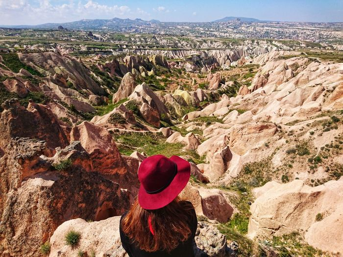 Rear view of woman wearing red hat against landscape