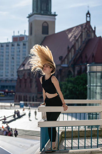 Beautiful Young Woman Tossing Hair On Balcony Against Buildings In City