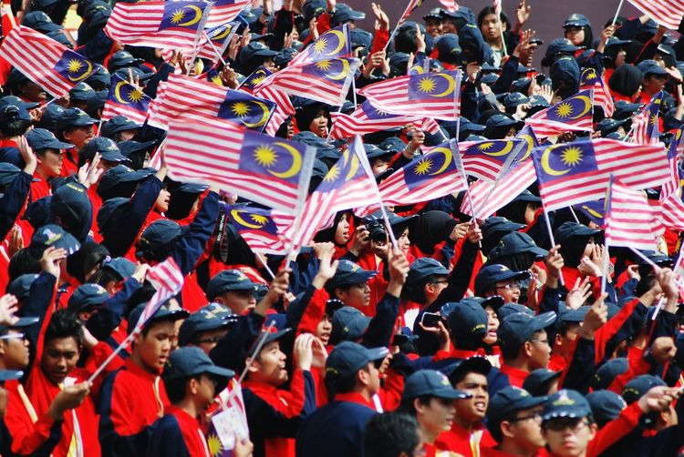 People with malaysian flags during celebration