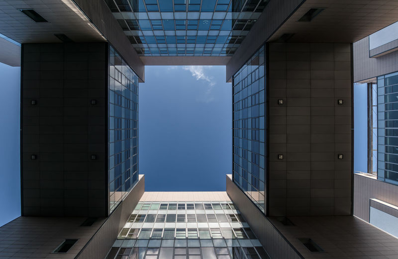 Directly below shot of modern glass building against sky