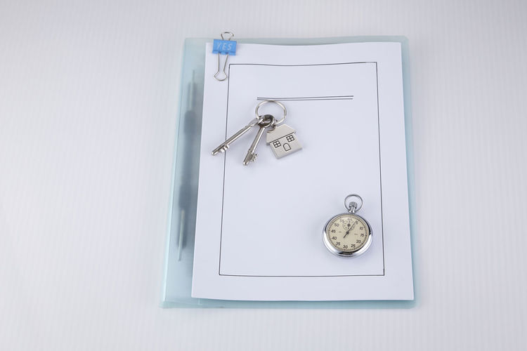 High angle view of house key and pocket watch on document