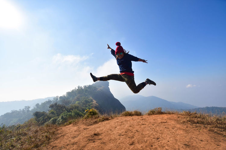 Full Length Of Woman In Mid-Air Over Mountain Against Sky